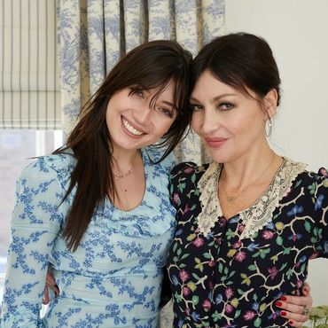 Pearl and Daisy Lowe standing next to each other in contrasting floral dresses