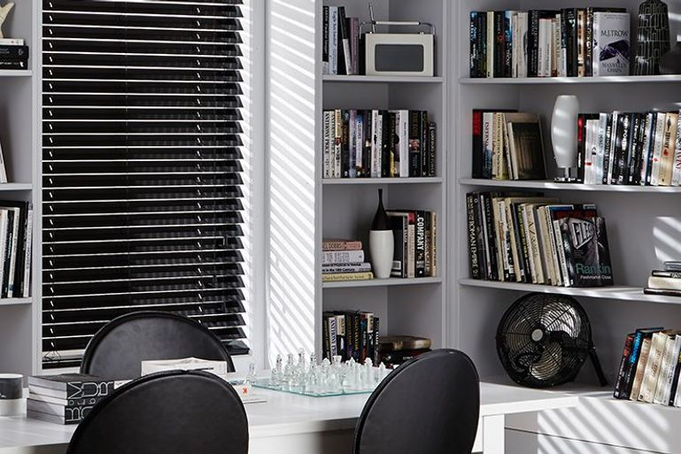 home office with monochrome decor, a white desk and bookcase and black venetian blinds