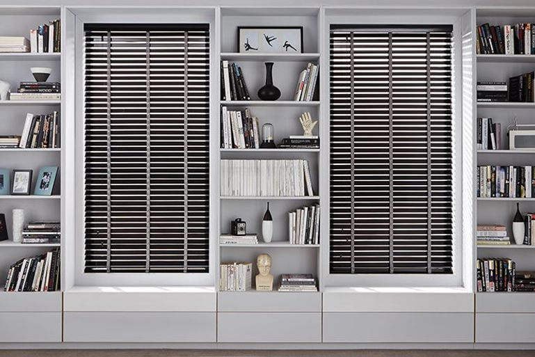 home office with built in white bookcases and two windows with black venetian blinds