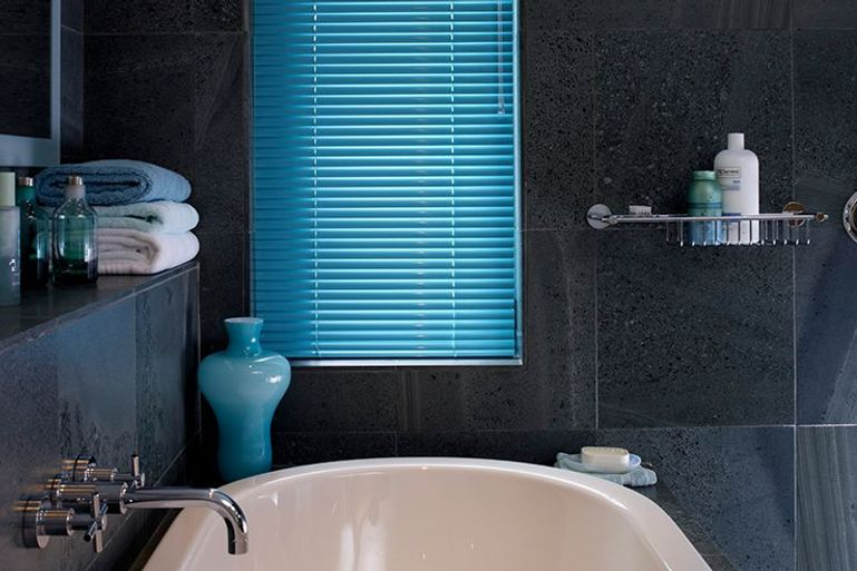 dark bathroom with contrast bright blue venetian blinds