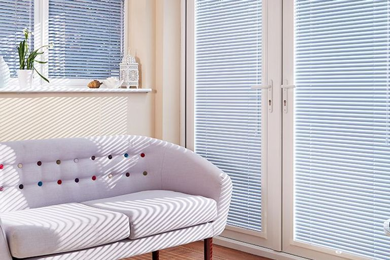 conservatory with soft lilac sofa and light blue venetian blinds