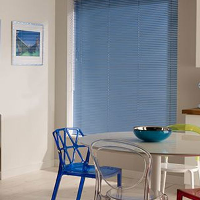 dining area with colourful dining chairs and blue venetian blinds