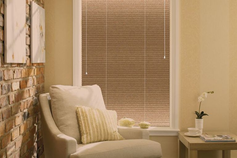 cosy cream armchair in front of a window with brown venetian blinds