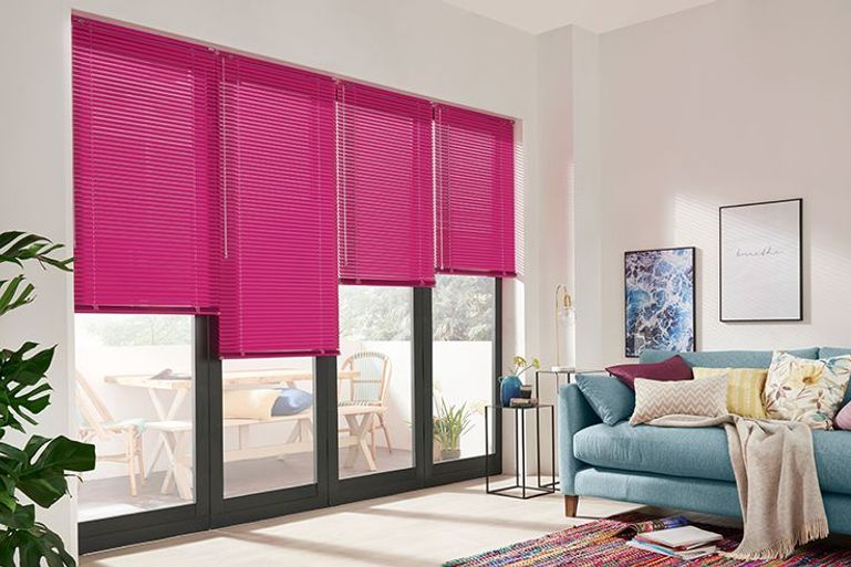 black bifold doors in a living room with contrast bright pink venetian blinds