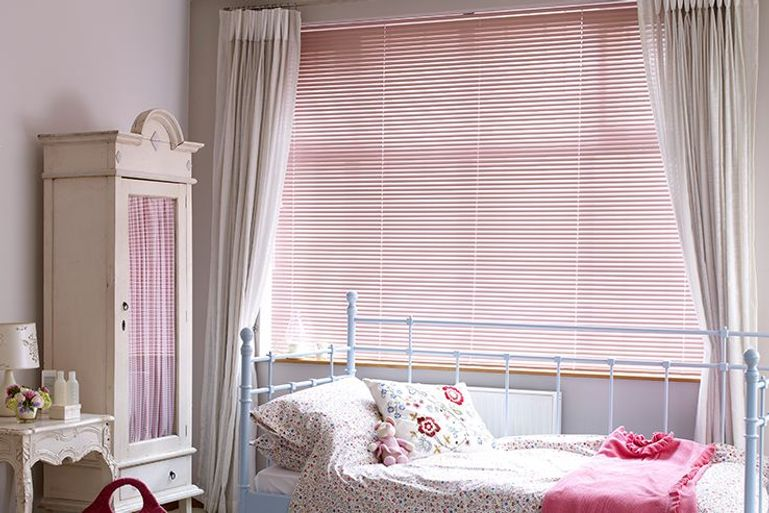 childs bedroom with pink venetian blinds and floral decor