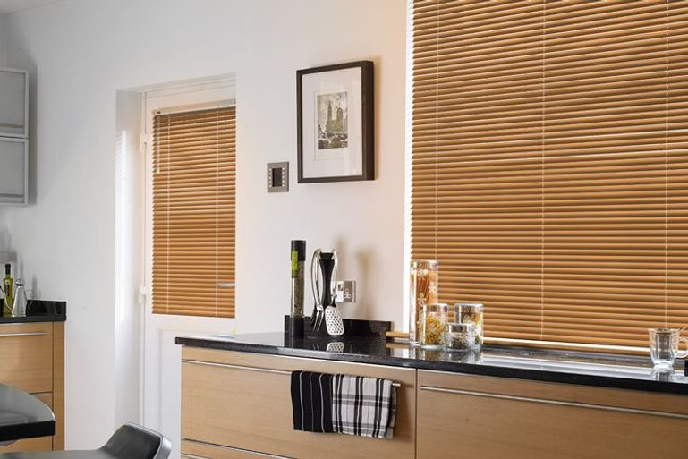 modern kitchen with wooden unit and orange venetian blinds