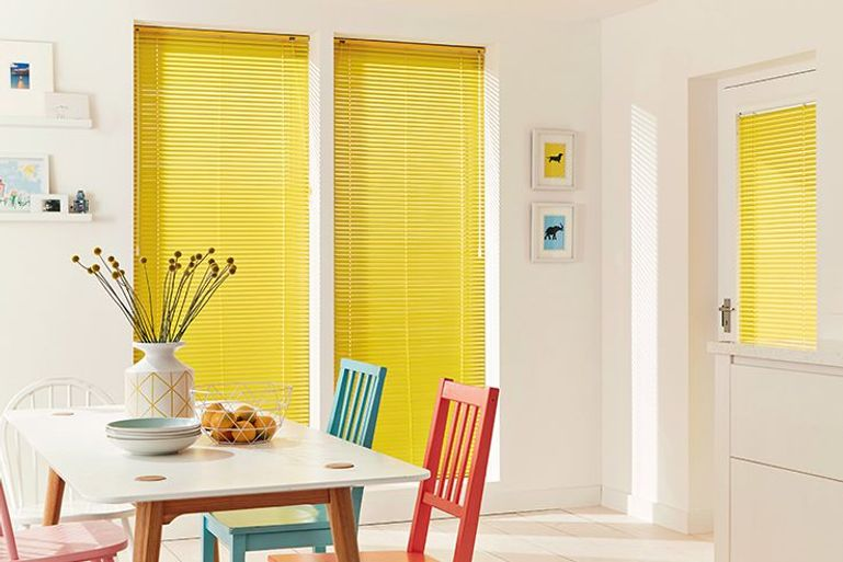 light and bright dining room with yellow venetian blinds
