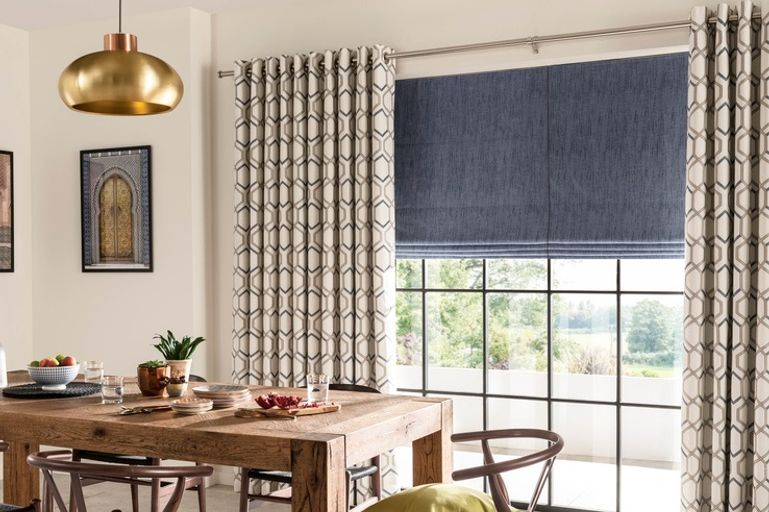 Blue roman window blind with cream curtains in the dining room