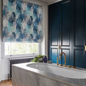 A blue bathroom with a large white bath in front of a window fitted with a Roman blind in Reflection Ocean fabric