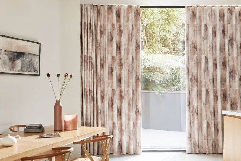 Dining room with patio doors dressed with patterned pink curtains