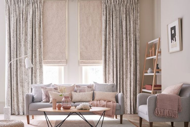 nude pink full length curtains and roman blinds in a luxuriously styled living room window