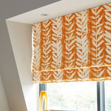 close up of orange patterned roman blind