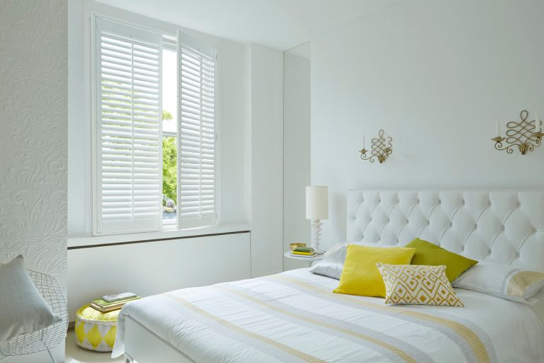 Large white Shutters cover a minimalist bedroom window