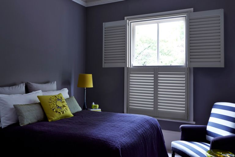 Grey tier-on-tier shutters in a modern bedroom. The Shutters are open at the top