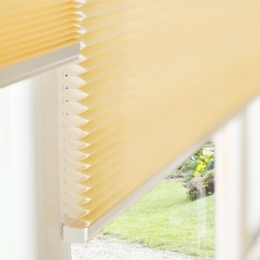 close up of yellow pleated blinds fitted in a window