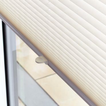 close up of white pleated blinds in a window