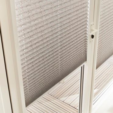 close up of grey pleated blinds in a patio door