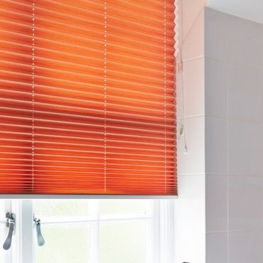 close up of orange pleated blinds