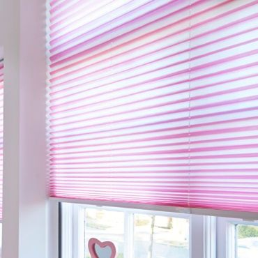 close up of bright pink roller blinds in a window