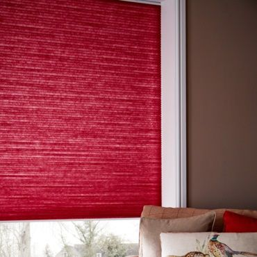 close up of red pleated blinds fitted in a window