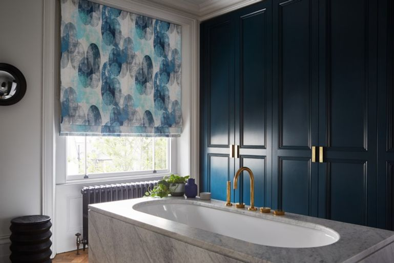 Luxury bathroom with patterned blue roman blinds