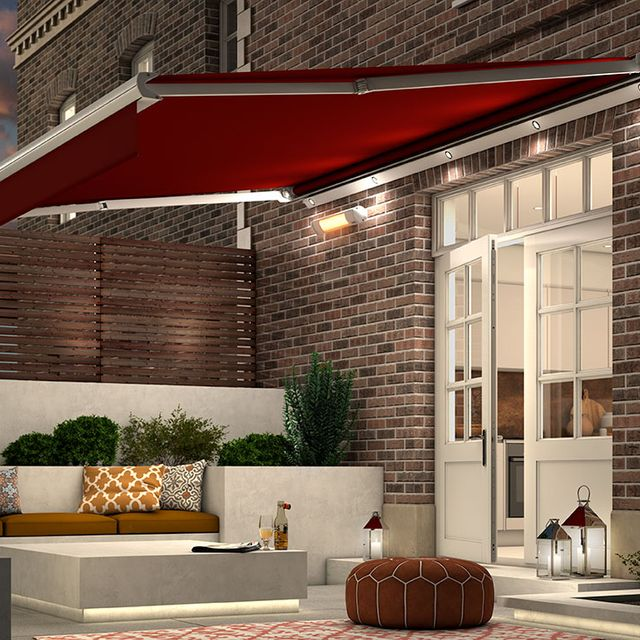 Garden Awning in Verona Rouge fabric extended over garden patio in the evening