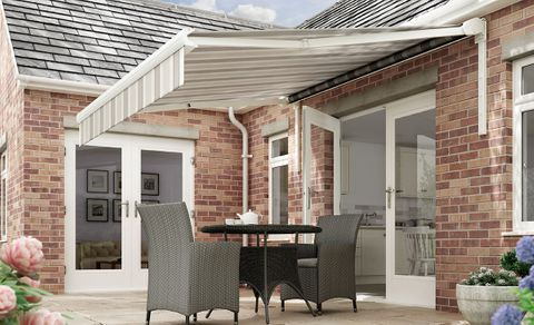 An extended awning in Hardelot Beige fabric covering an outdoor patio area set with a table and chairs