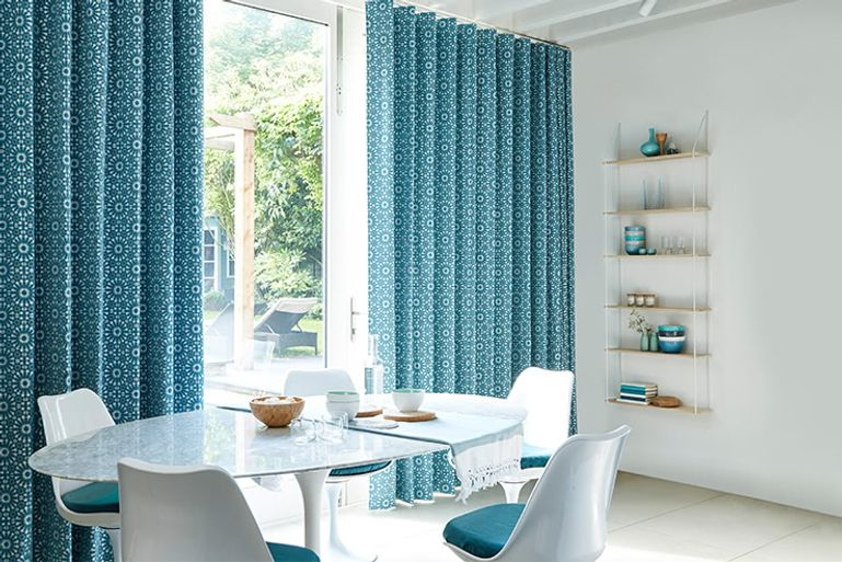 teal blue full height curtains in a modern dining room window