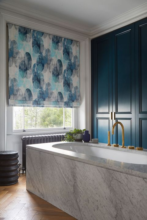 Bright blue blinds with sphere patterns in a luxuriously decorated bathroom window
