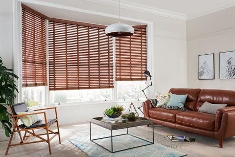 Modern sophisticated living room with bay window dressed with dark brown wooden blinds