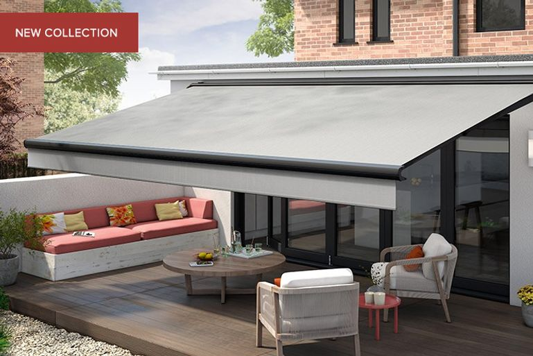 Grey awning covering a wooden decked outdoor area with a small table and chairs