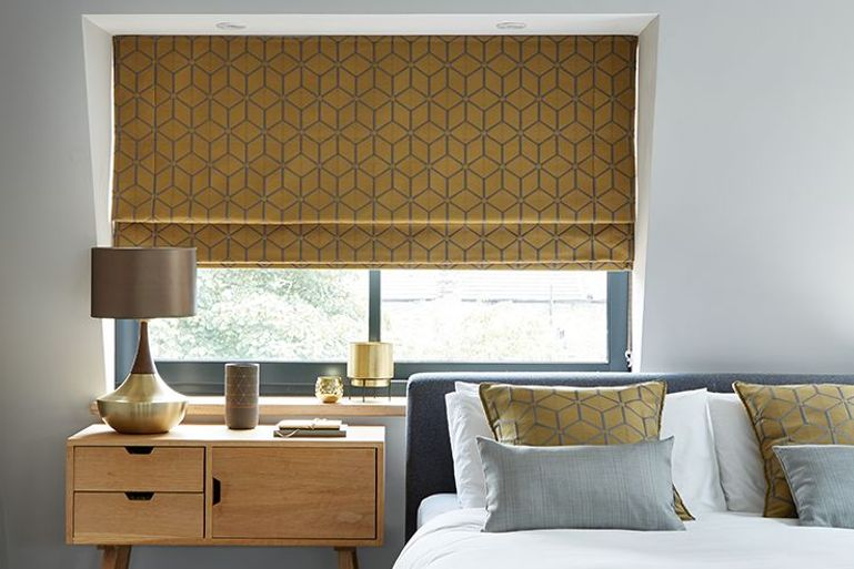 nexus brushed gold geometric pattern roman blinds in a bedroom window