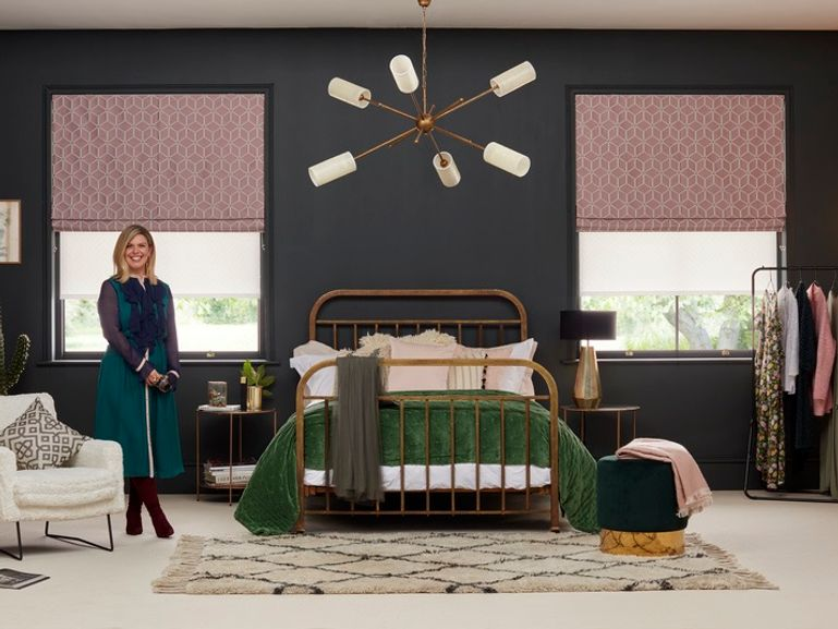 Someone stood in a bedroom with navy blue walls and pink roller blinds with a repeating geometric pattern which are fitted to rectangular windows either side of the bed