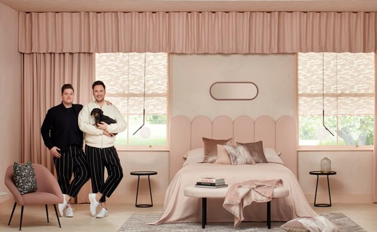A bedroom decorated with blush and white colours has blush coloured curtains that span across two rectangular windows