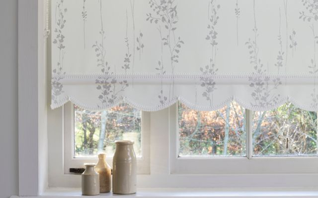 White roller blind fitted to a large window with a simple repeating leaf pattern in grey