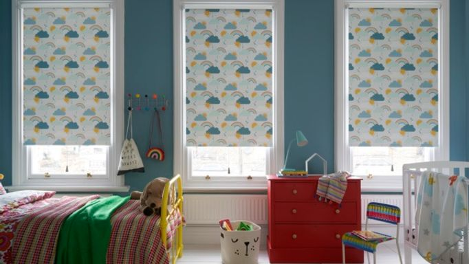 A child's bedroom with 3 windows, each fitted with a Roller blind in Rainbow Dreams Multi Colour fabric