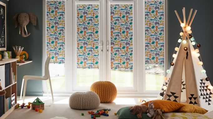 Multicoloured roller blinds attached to door windows in a kids bedroom which has cushions and a tent with bauble lights attached to it
