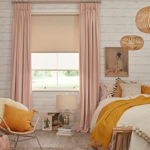 Pink blush curtains over white roller blinds in a bedroom