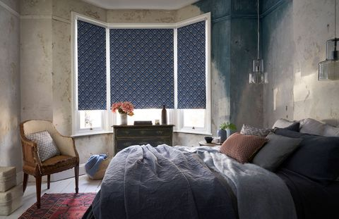 Blue Patterned roller blind hung in shabby chic bedroom