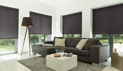 Plain black roller blinds hung in living room