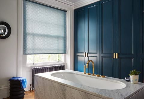 Blue patterned Vesper Crystal Blue roller blinds hung in bathroom