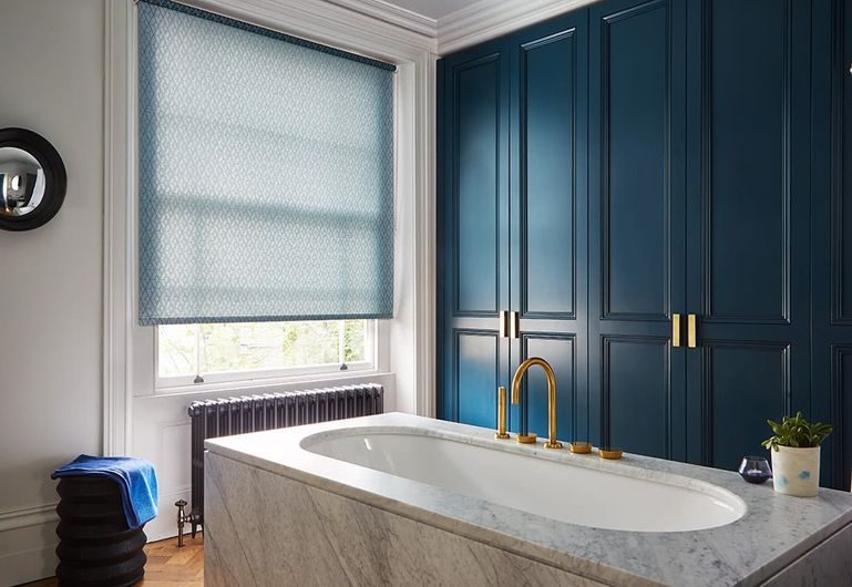 Blue patterned roller blinds hung in bathroom