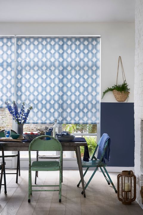 Patterned blue roller blind hung in dining room