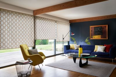 Brown pattern roller blind hung in colourful retro living room