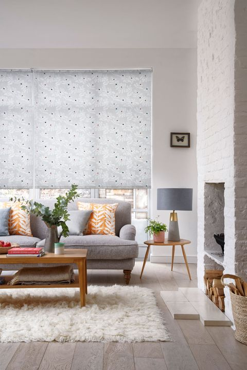 Leaf pattern roller blinds hung in a cosy natural living room