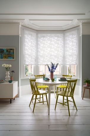 Dining area with yellow statement chairs and a window dressed with white Leaf pattern roller blinds