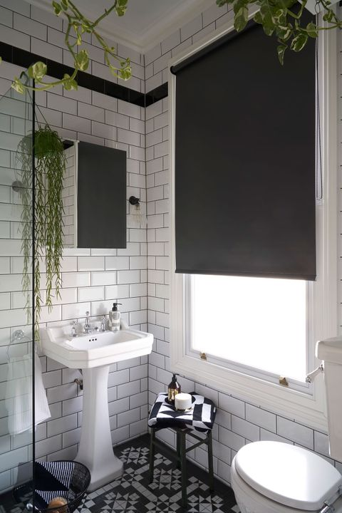Plain grey roller blind hung in bathroom with monochrome decor
