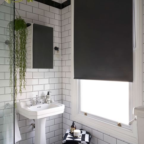 Black roller blind hung in bathroom with monochrome decor