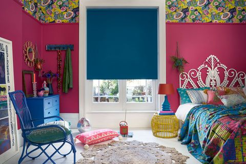 Plain blue Cordova Peacock roller blind hung in a bright pink  bedroom