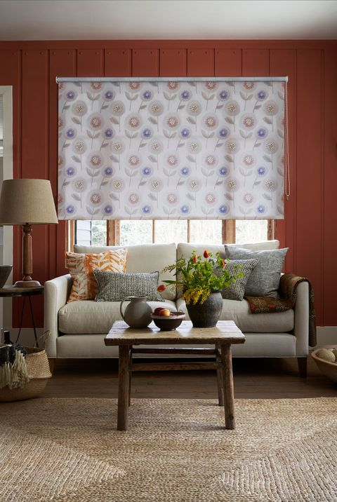 Rustic living room with natural jute rug and window dressed with floral cream roller blind